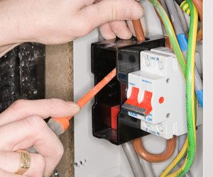 An electrician fixing a fuse box